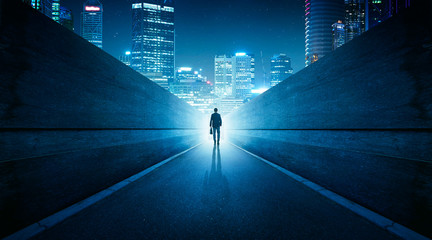 Ambitions concept with businessman walking from alley to modern city . Night scene . Wall mural