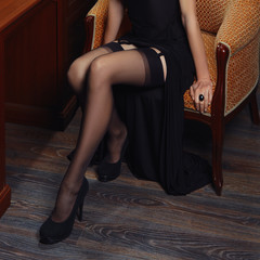 Beautiful female legs in stockings with suspender belt sitting in armchair near the desk