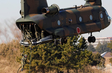 Members of Japan's Ground Self-Defense Force 1st Airborne Brigade descend from a CH-47 helicopter during an annual new year military exercise at Narashino exercise field in Funabashi