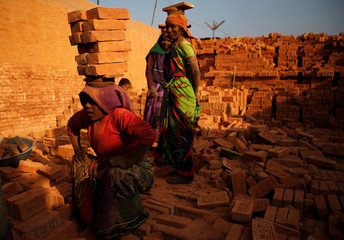 A worker stands as she carries bricks on her head at a brick factory in Bhaktapur