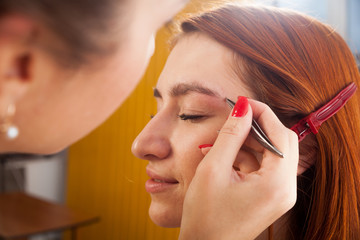 Close-up make-up artist plucks his eyebrow tweezers young red-haired woman