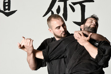 Two fighters of martial art (Ju-Jitsu) with black kimono and black belts
