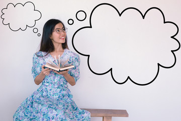 A cute Asian Woman Wearing Vintage blue dress sitting and reading on the bench, thinking with speech bubbles