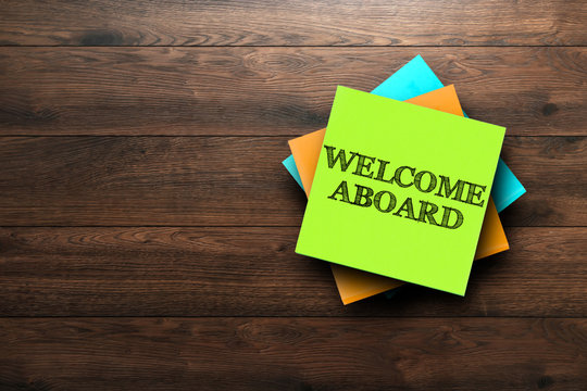 Welcome Aboard, the phrase is written on multi-colored stickers, on a brown wooden background. Business concept, strategy, plan, planning.