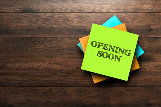 Opening Soon, the phrase is written on multi-colored stickers, on a brown wooden background. Business concept, strategy, plan, planning.