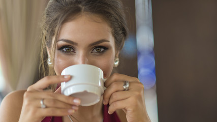 Young stylish business woman drinks coffee She is sexy and sensual. Smiling. Dreaming.