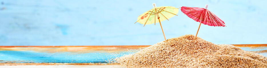 Close-up of two cocktail umbrellas on sand