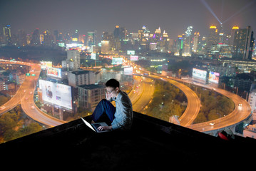 Asian businessman using phone and laptop with city  background, technology communication concept