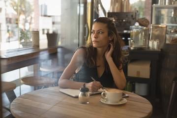 Woman writing on diary in coffee shop