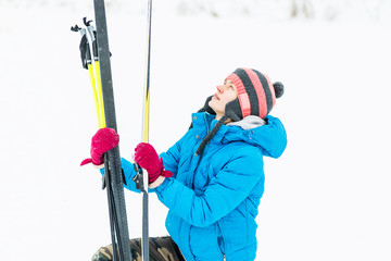young caucasian woman checking her ski equipment outside in winter