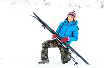 happy young woman outside with a pair of skis