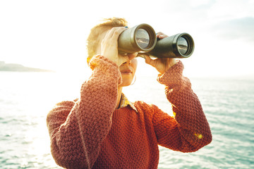 Beautiful Young Girl Looking Through Binoculars At The Sea On A Bright Sunny Day. Wanderlust Journey Concept