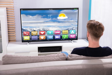 Man Watching Television Showing Colorful Application