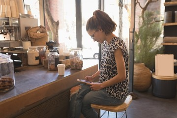 Woman using digital tablet at counter