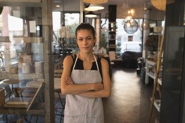 Waitress standing with arms crossed in coffee shop