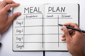 Person Filling Meal Plan In Notebook