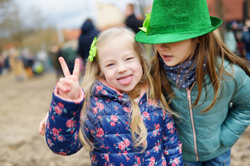 Two cute girls wearing green hats and accessories celebrating St. Patrick's day in Vilnius.