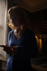 Woman using her mobile phone in a dark room