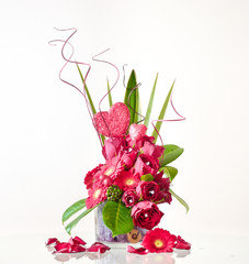 Valentine's Day flower composition with heart and with rose petals