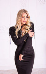 Beautiful sexy blonde in  black dress posing on white background. Elegant young woman.