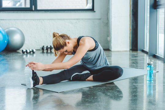 sportswoman stretching on mat after workout in gym