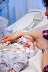 Shallow depth of field of sick infant boy undergoing a electrocardiography to check his heart.