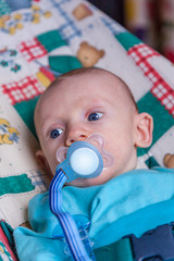 Infant boy with a pacifier lying down and looking to the side.