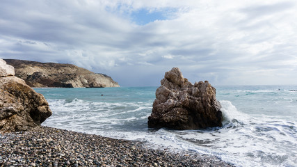 Image of sea, pebble beach, rocky slope, cloudy sky