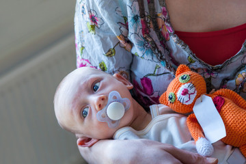 Infant boy child with a pacifier lies in his mothers arms with a orange knitted stuffed toy cat.