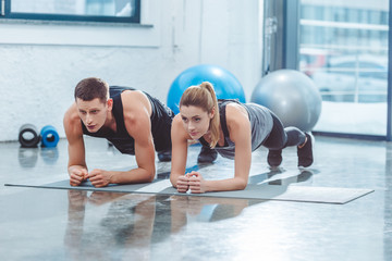 sporty young couple doing plank exercise in gym