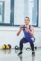 athletic young woman doing squat exercise and holding dumbbell in gym