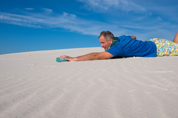 Exhausted man is crawling on the sand