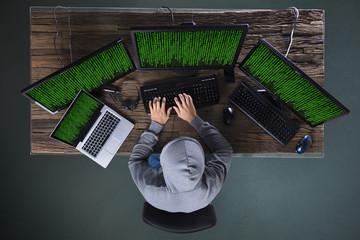 Hacker Hacking Multiple Computers On Desk