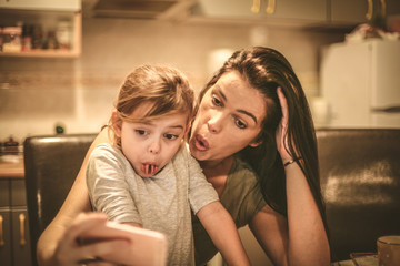 Funny mother and daughter have fun together.
