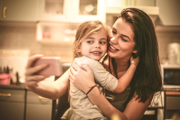 Beautiful portrait of mother and daughter taking a self portrait with phone.
