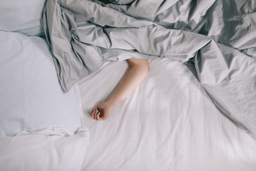 cropped image of girl sleeping on bed covered with blanket
