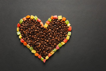 Colorful candied fruits in the form of heart with brown coffee beans isolated on black background for design. Saint Valentine's Day card on fabruary 14, holiday concept. Copy space for advertisement.