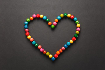Colorful wooden beads in the form of heart isolated on black background for design. Saint Valentine's Day card on fabruary 14, holiday concept. Copy space for advertisement.