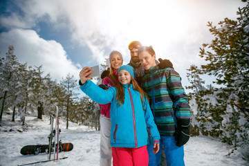 family laughing and making selfie with mobile on winter ski vacation