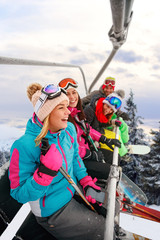 cheerful friends skiers on ski lift ride up on ski slope at snowy day