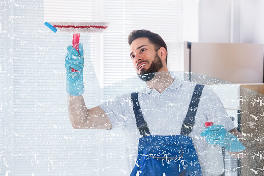 Janitor Cleaning Window With Squeegee