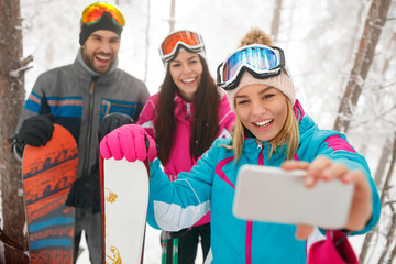 friends snowboarders or skiers making selfie in fog forest