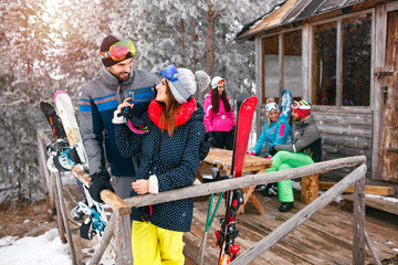 couple with friends spending holiday in winter snow cottage
