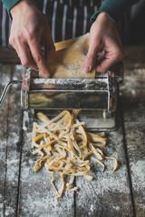 Female preparing homemade tagliatelle with machine,selective focus