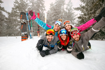 group of skiers lying on snow and having fun