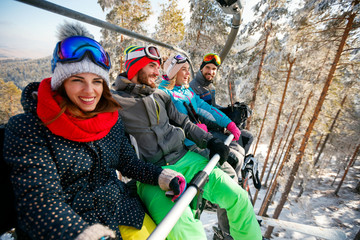Smiling friends skiers and snowboarders on ski lift