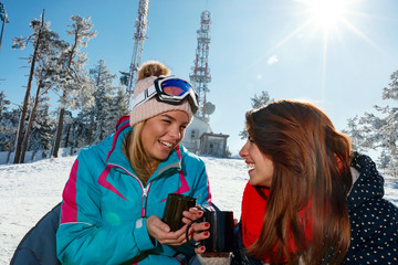 female friends enjoying hot drink in cafe at ski resort