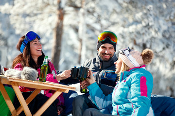 winter holidays – Smiling friends drinking beer on break at ski resort