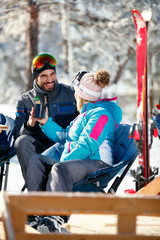 Couple spending time together and drink after skiing in cafe at ski resort
