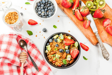 Healthy breakfast with muesli or granola with nuts and fresh berries and fruits - strawberry, blueberry, kiwi, on white table, copy space